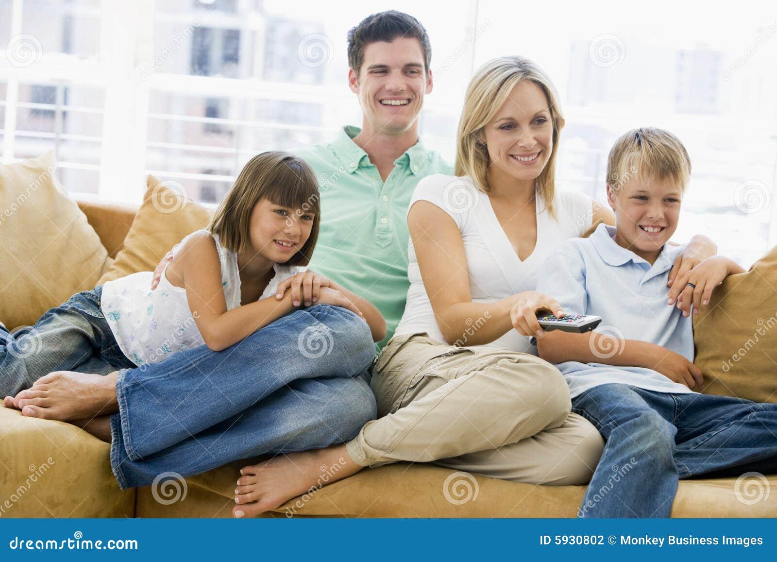 Familie, Die Im Wohnzimmer Mit Fernsteuerungs Sitzt Stockfoto - Bild ...