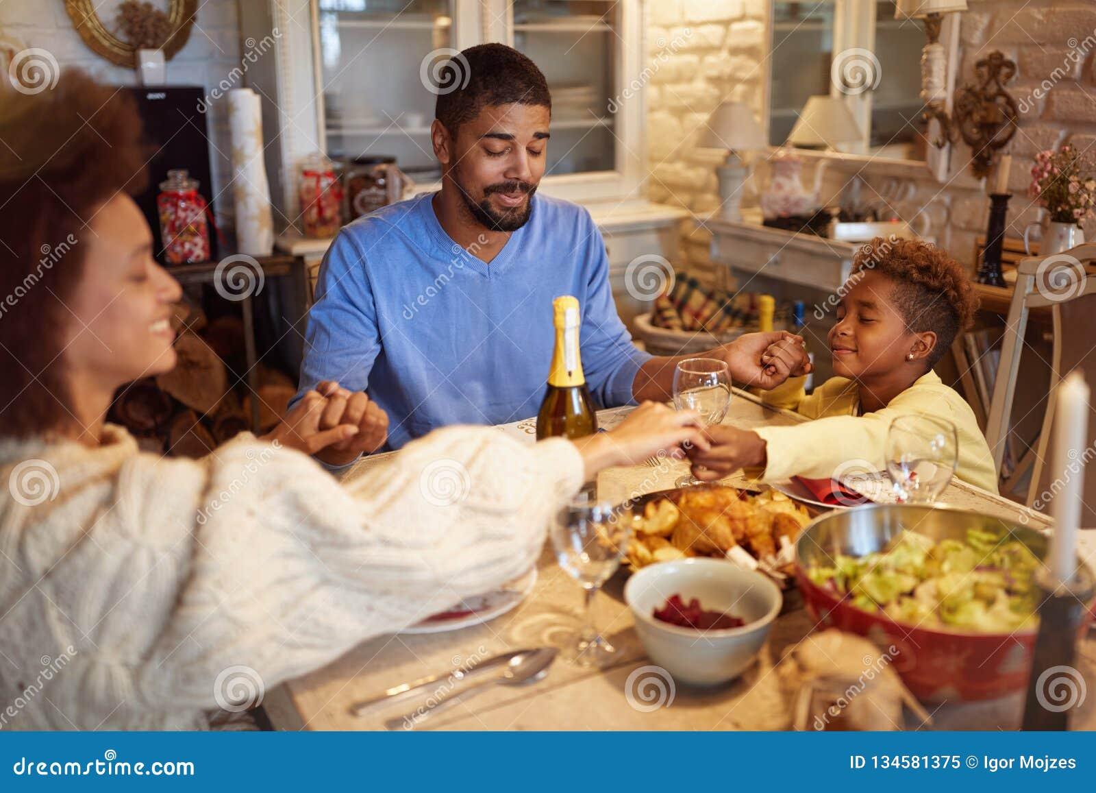 Familie die Kerstmisgebed voor diner hebben thuis