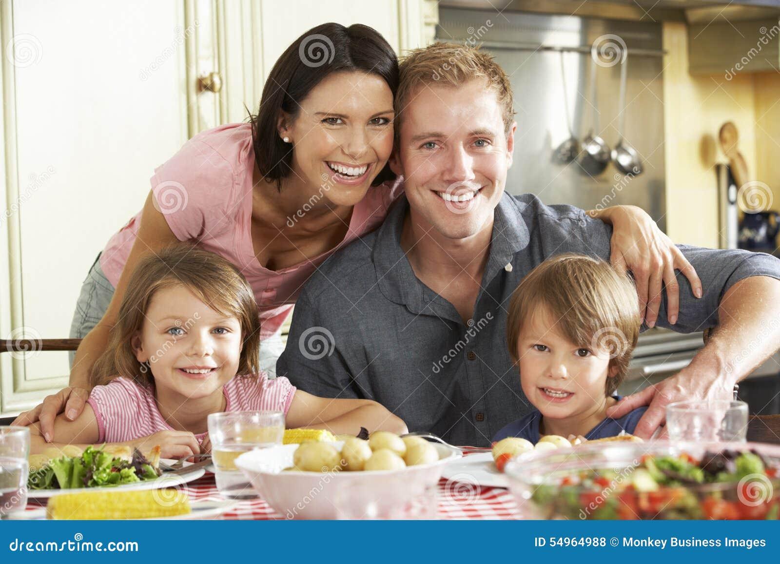 Familie die Maaltijd samen in Keuken eten