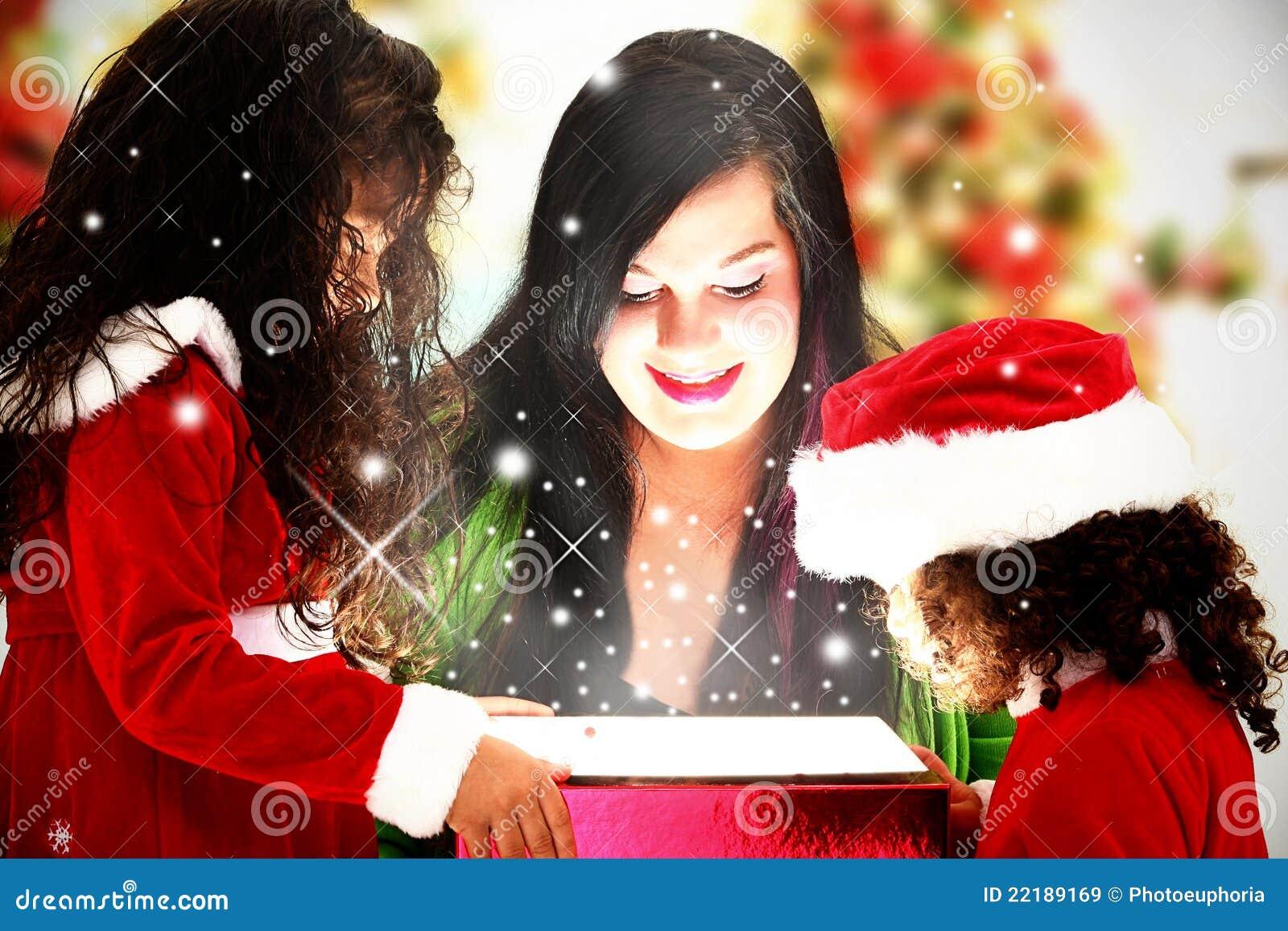 Familie, die magisches Weihnachtsgeschenk öffnet