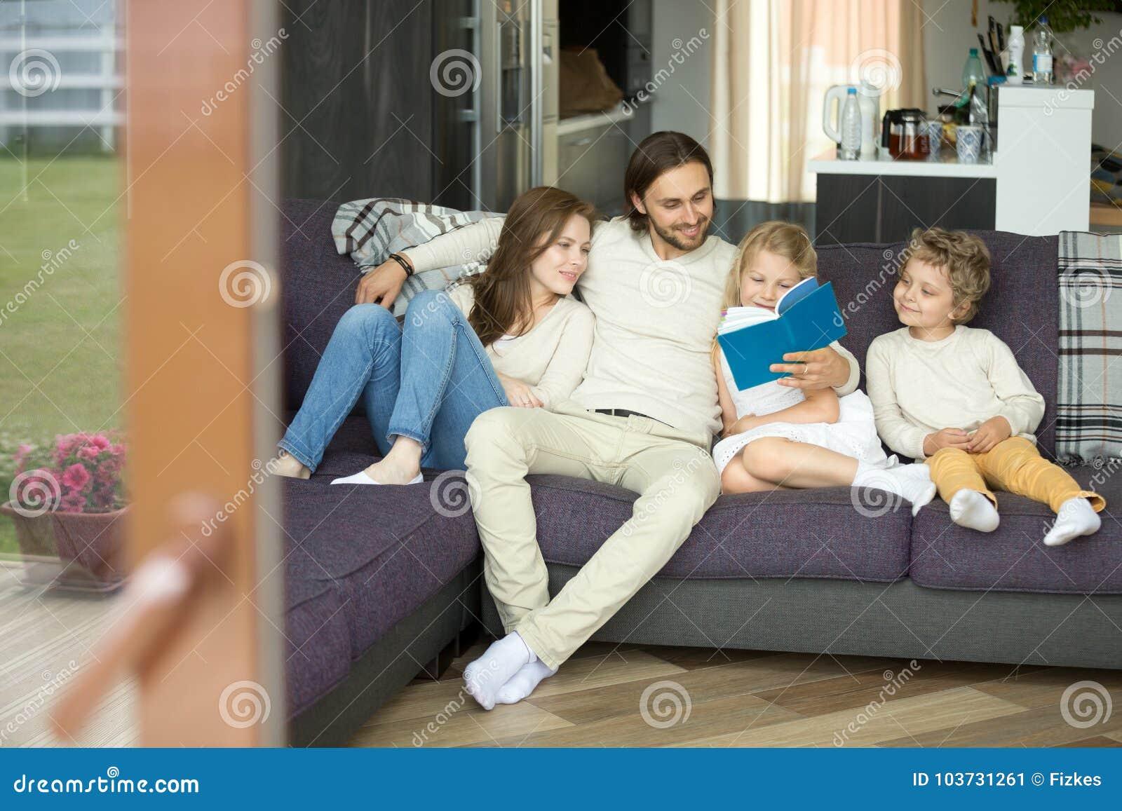 Familie die met jonge geitjes boekzitting op bank thuis lezen