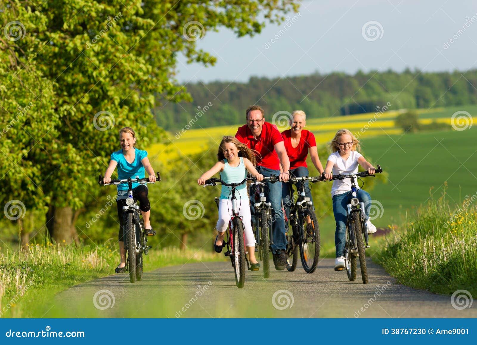 Familie die met jonge geitjes in de zomer met fietsen cirkelen