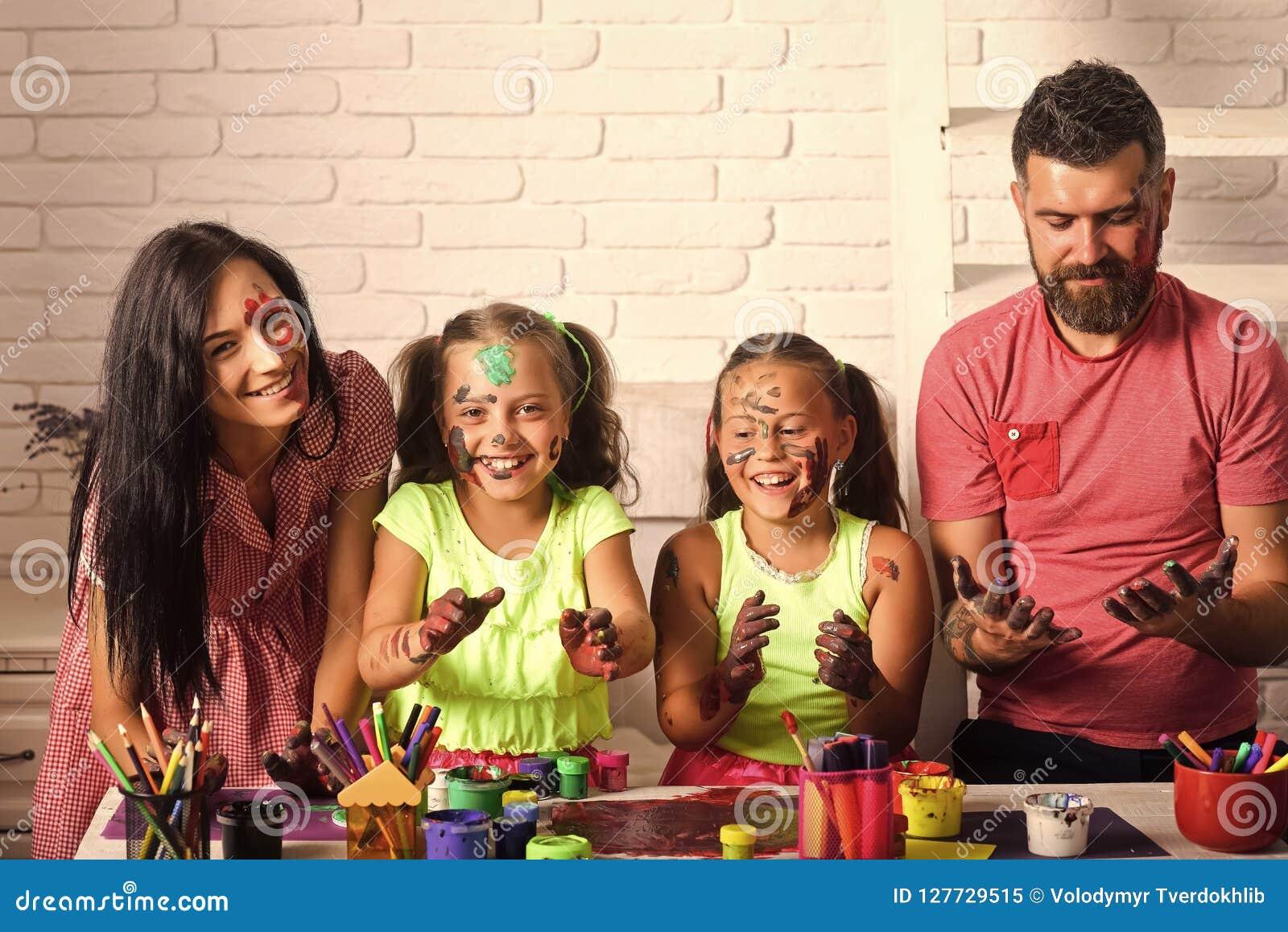 Familie, die mit den Händen gefärbt in den Farben lächelt