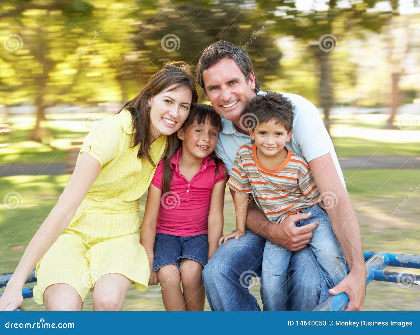 Familie die op Rotonde in Park berijdt