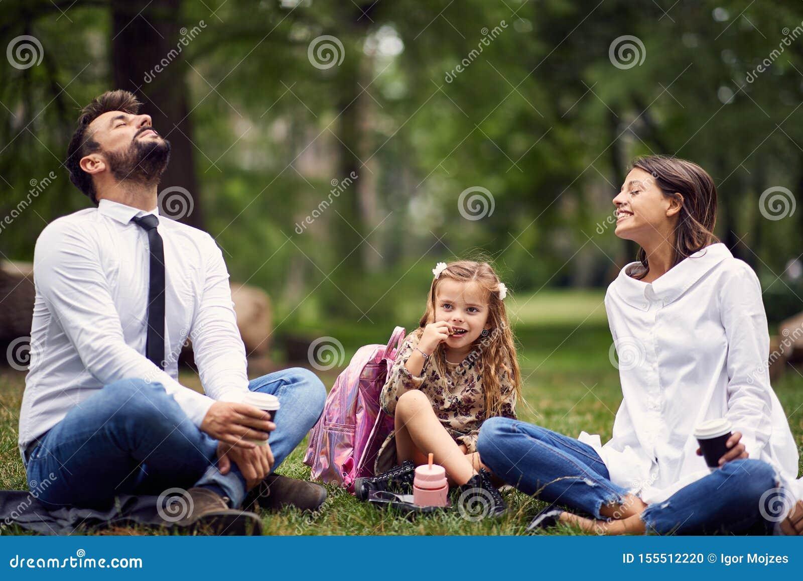 Familie die in park na school en het werk rusten