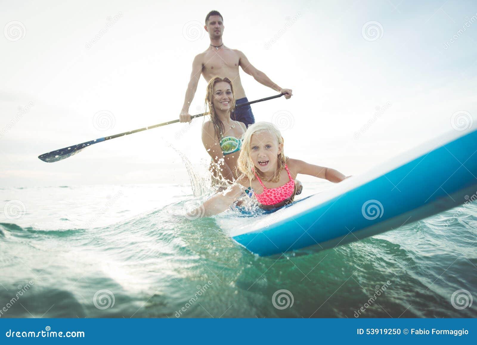 Familie die peddelbranding in de oceaan maken