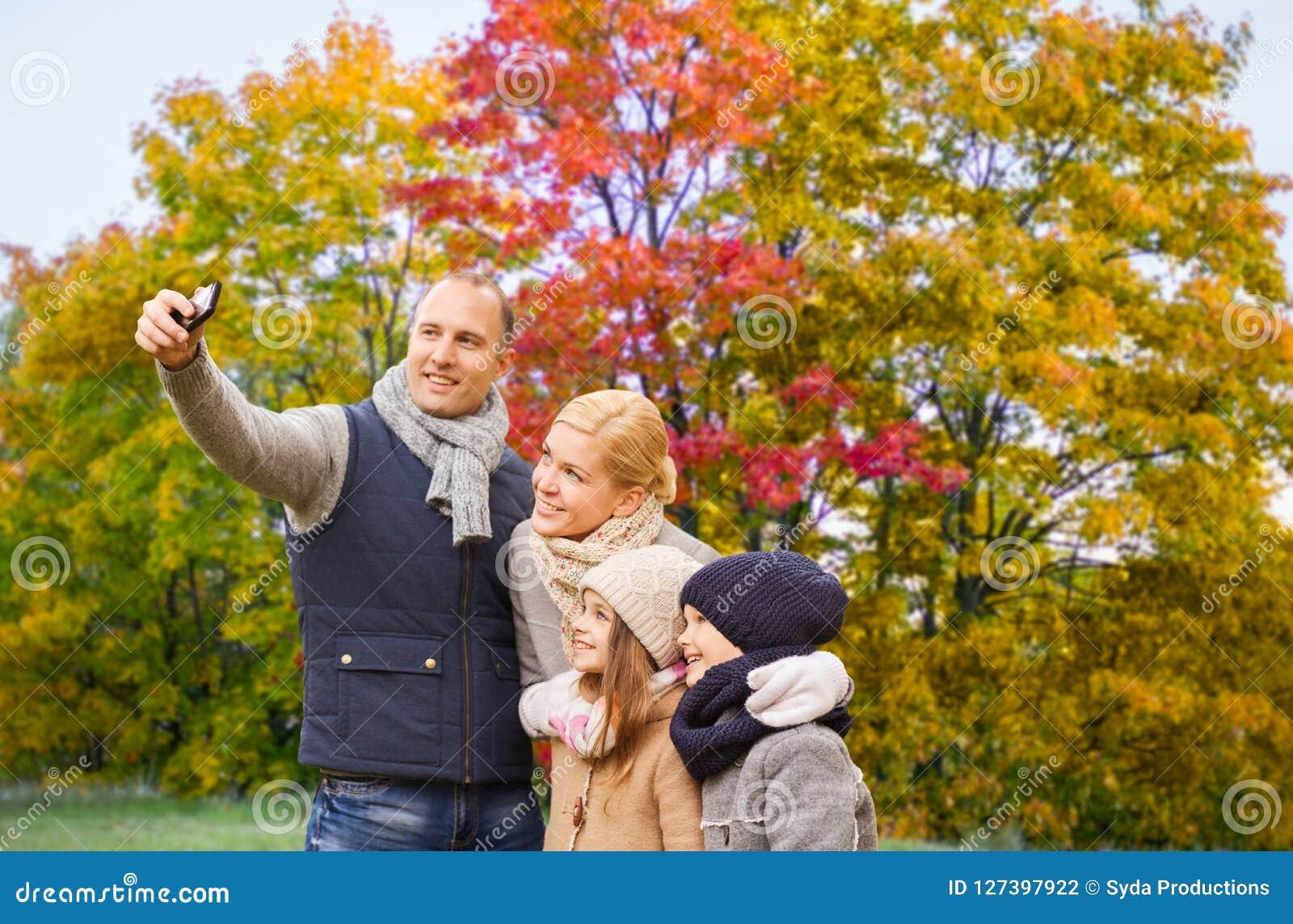 Familie, die selfie durch Smartphone im Herbstpark nimmt