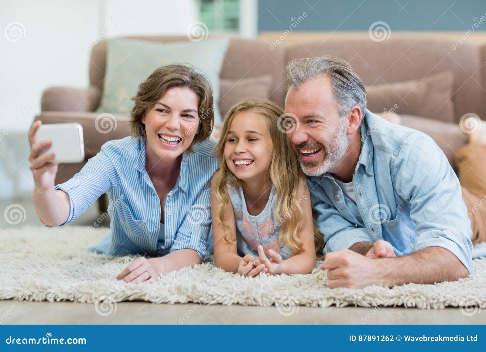 Familie die selfie uit mobiele telefoon nemen terwijl het liggen samen op tapijt in woonkamer