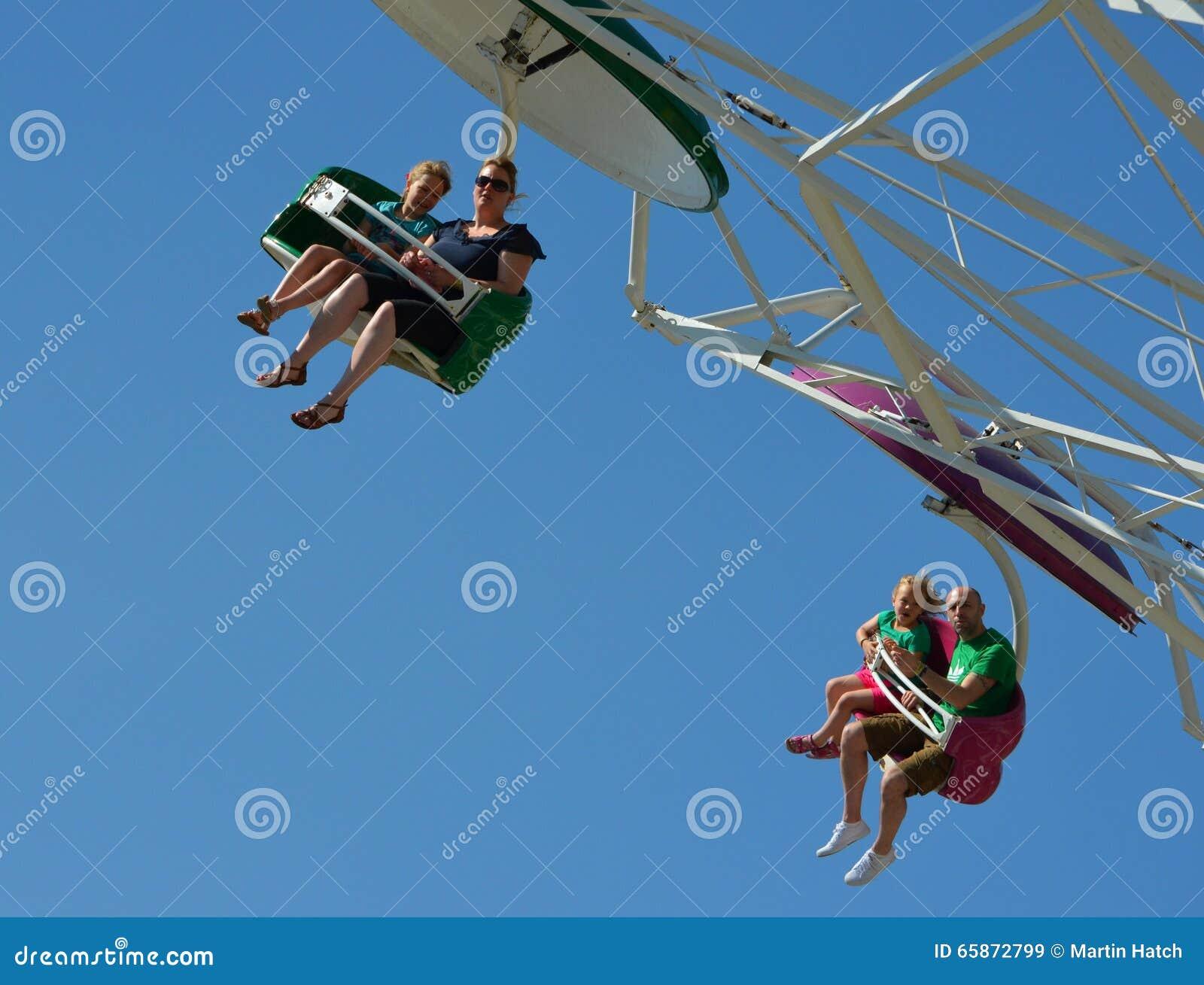 Familie, die Spaß auf der Fallschirmjägerrummelplatzfahrt hat