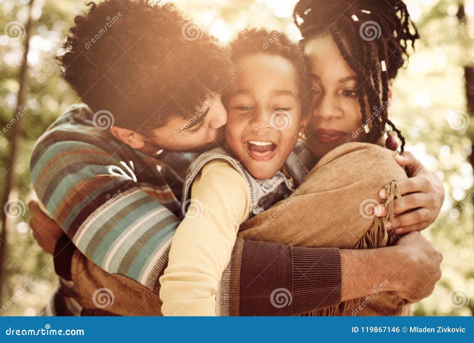 Familie die van in omhelzing samen in aard genieten