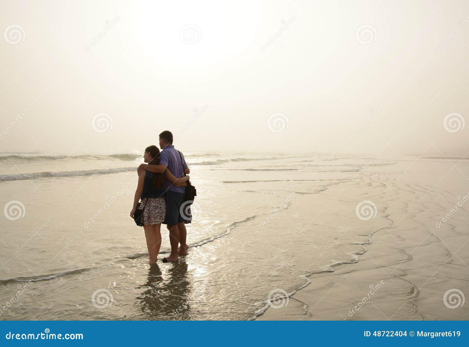 Familie die van tijd samen op mooi mistig strand genieten