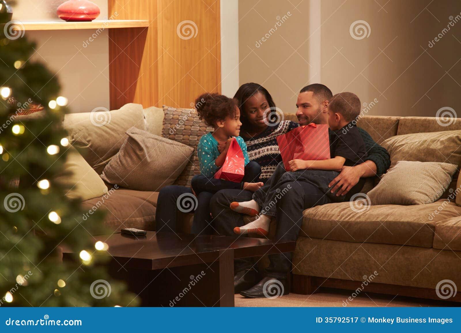 Familie, die zu Hause das Weihnachten angesehen von der Außenseite feiert