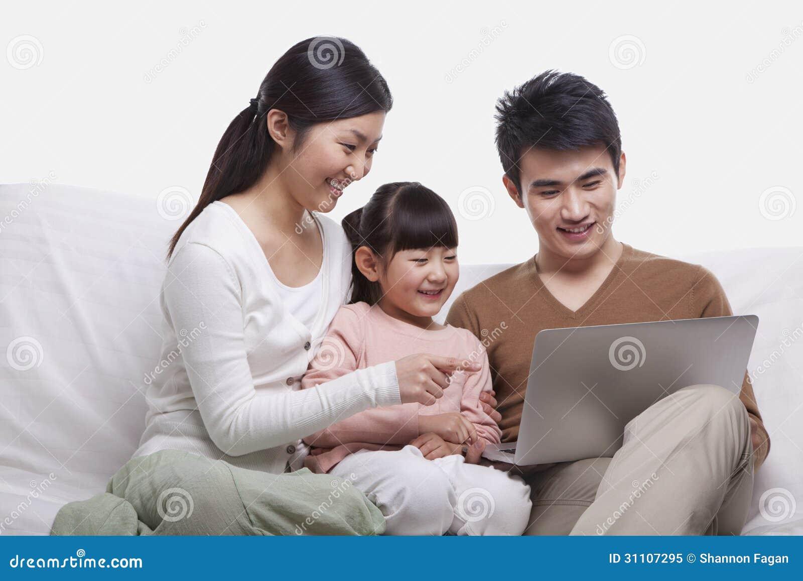 Familie, die zusammen auf dem Sofa betrachtet Laptop, Atelieraufnahme lächelt und sitzt
