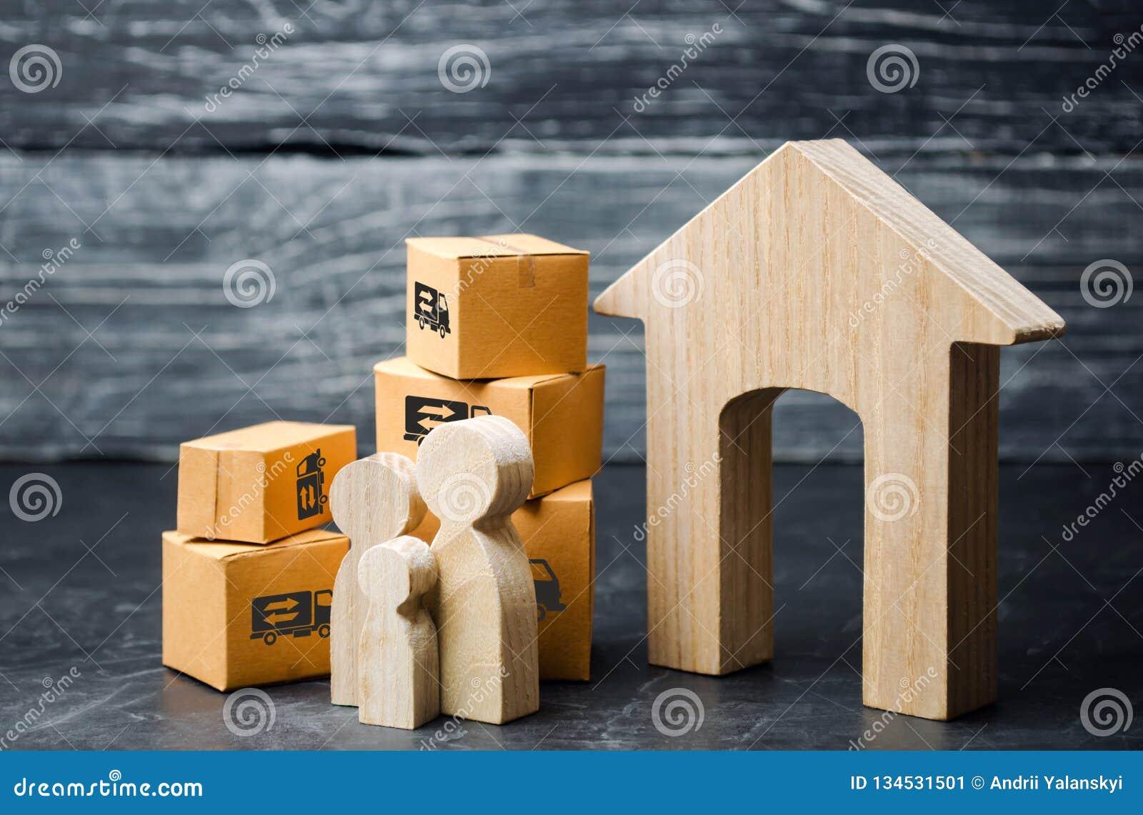 Familie en kartondozen dichtbij het huis Het concept zich het bewegen aan een nieuw huis, verhuizing Het gaan naar een ander stad