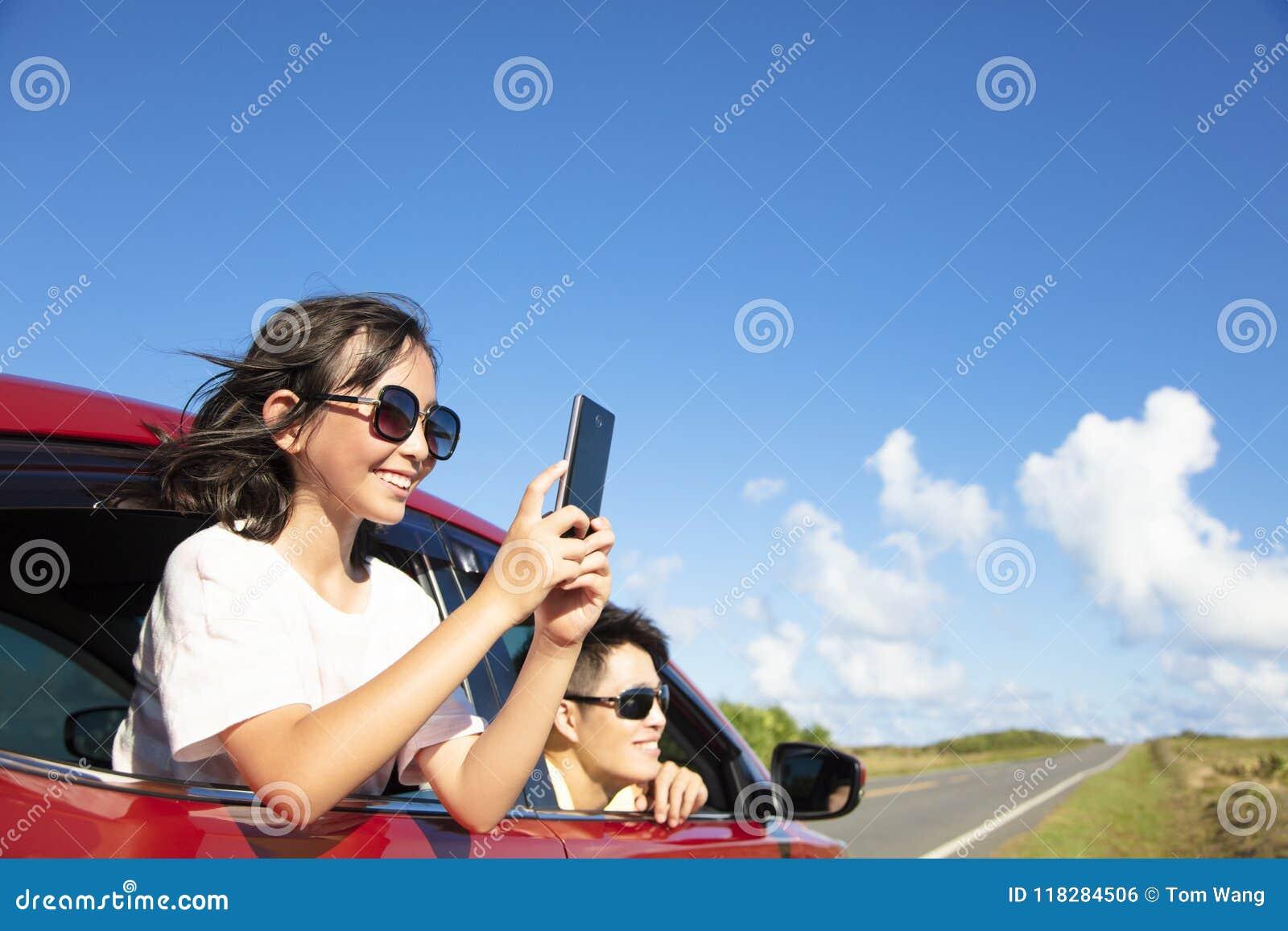 Familie genießen die Autoreise, die Foto durch intelligentes Telefon macht
