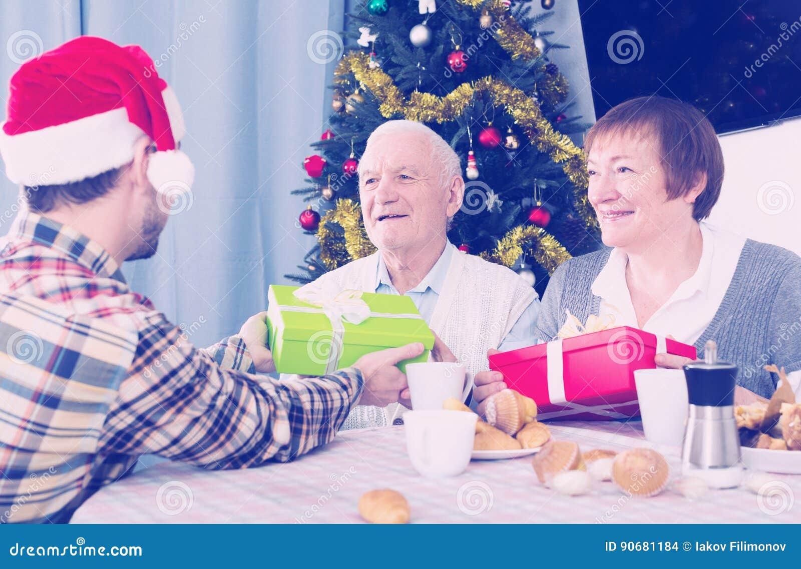 Familie Gibt Weihnachtsgeschenke Stockfoto - Bild von paare, älter ...