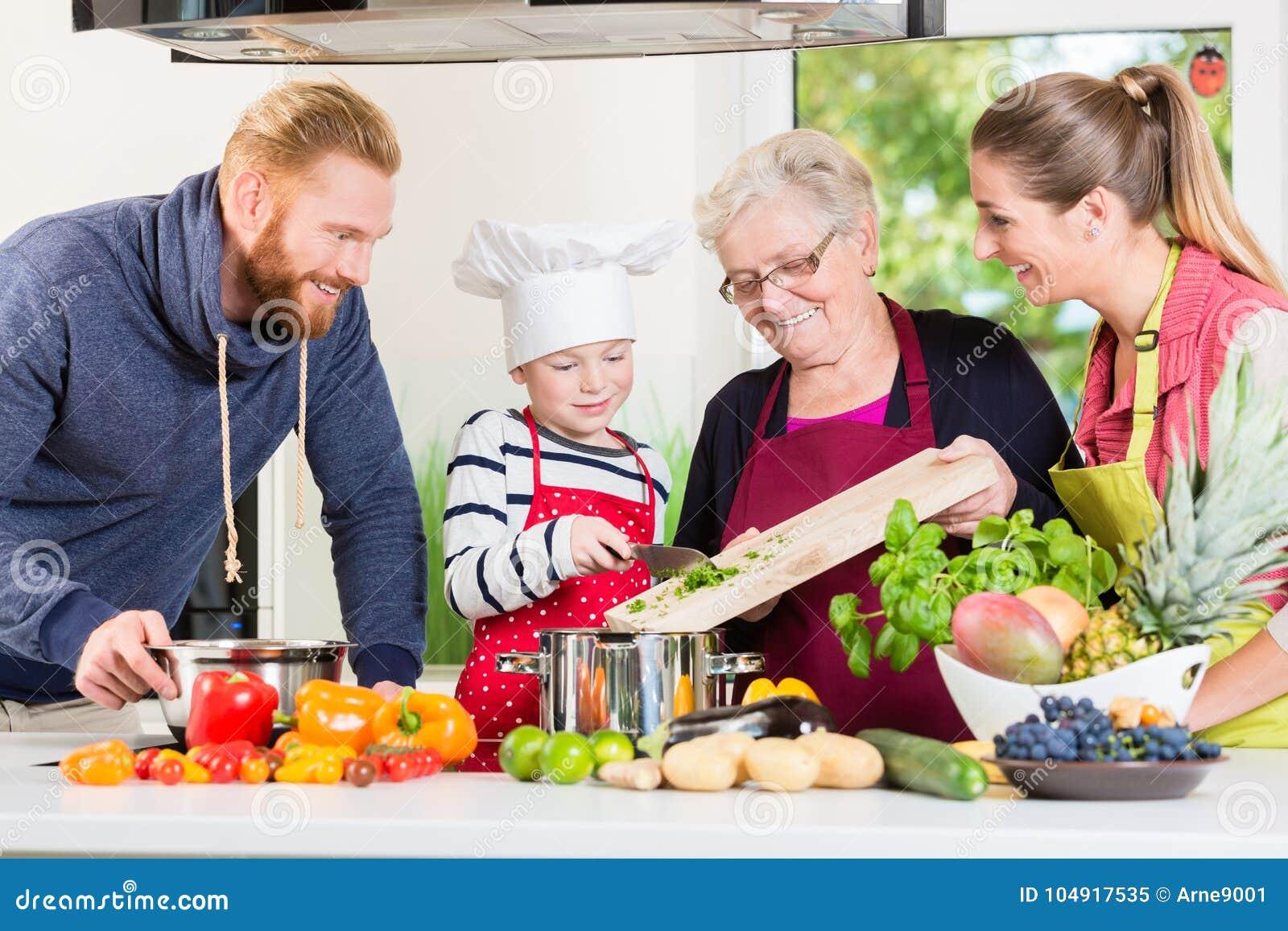 Familie het koken in multigenerationeel huishouden met zoon, moeder,