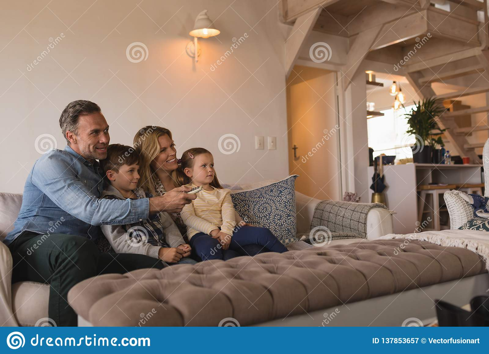 Familie het letten op televisie in woonkamer thuis