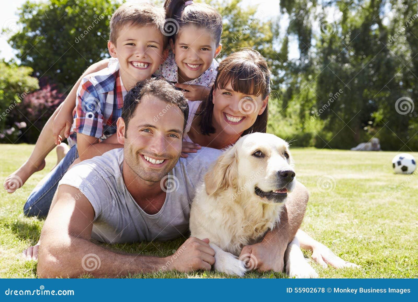 Familie het Ontspannen in Tuin met Huisdierenhond