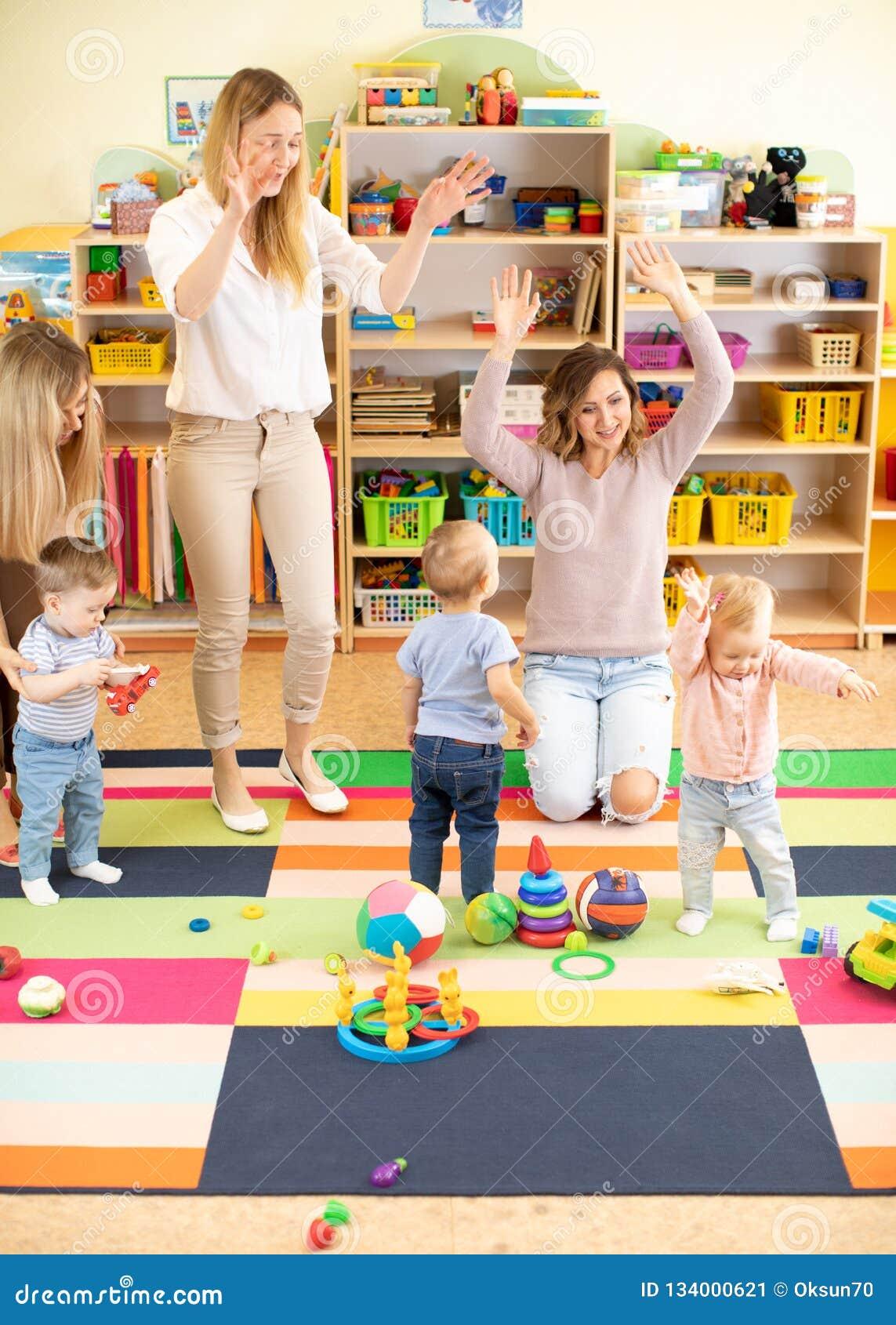 Familie, kinderjaren, activiteiten en creativiteitconcept - gelukkige ouders en hun kleine jonge geitjes die een pret in speelkam