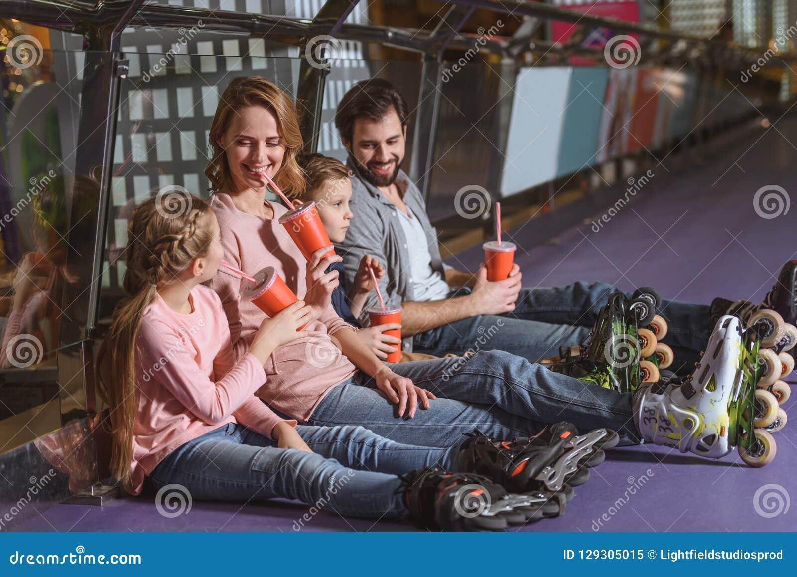 Familie met dranken die na het schaatsen rusten
