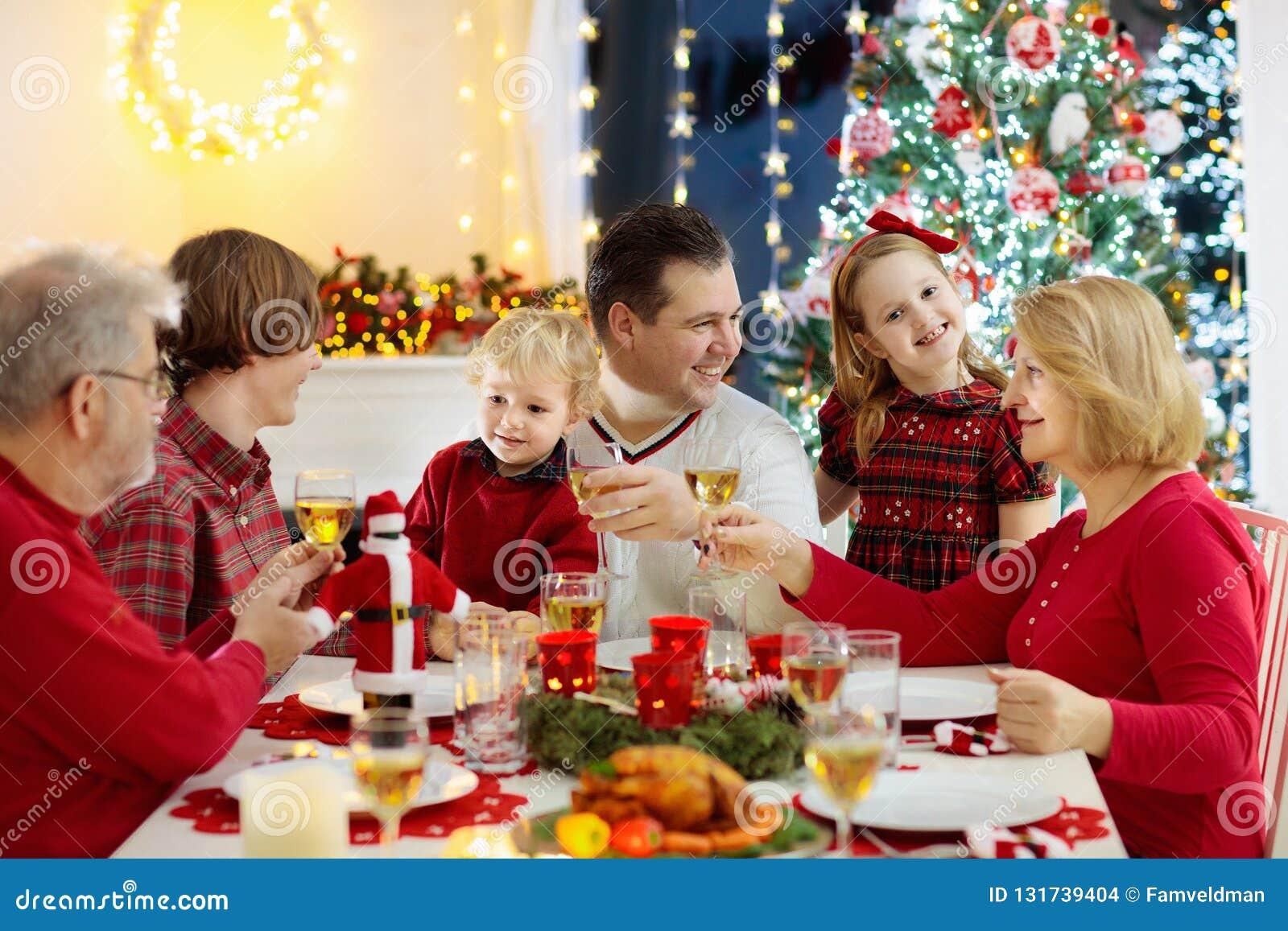 Familie met kinderen die Kerstmisdiner eten bij open haard en verfraaide Kerstmisboom Ouders, grootouders en jonge geitjes bij fe