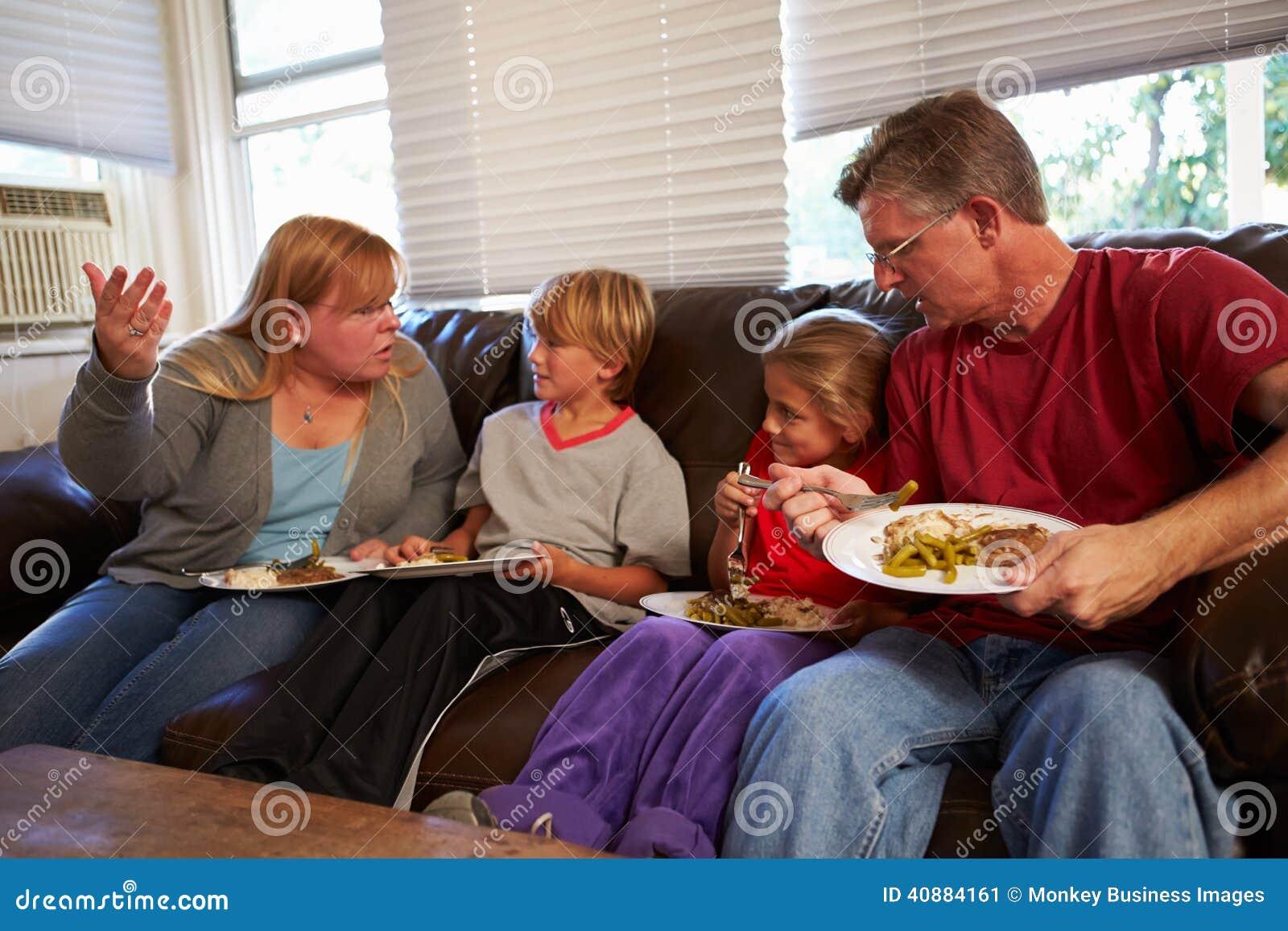 Familie met Slecht Dieet Sit On Sofa Eating Meal en het Debatteren