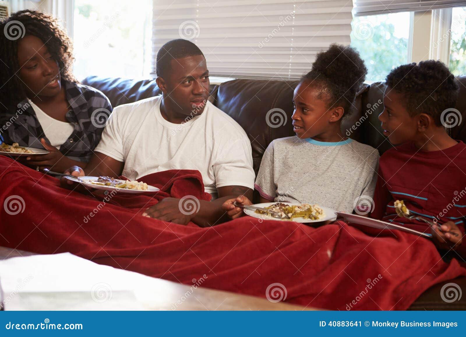 Familie met Slechte Dieetzitting op Sofa Eating Meal