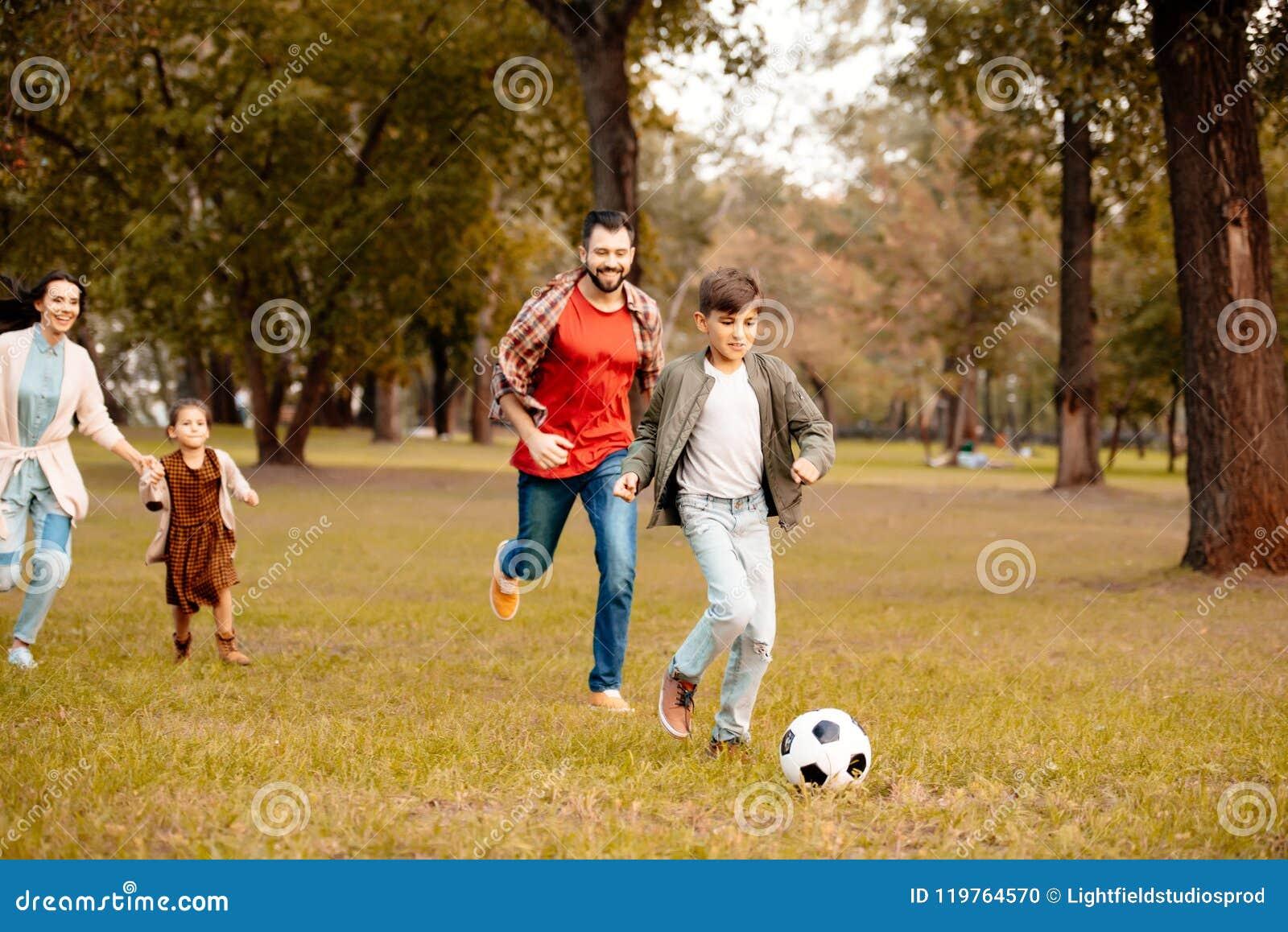 Familie met twee kinderen die en voetbal samen in in werking stellen spelen