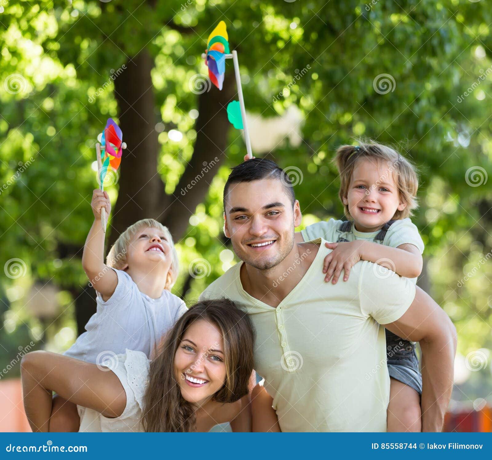 Familie mit Spielzeugwindmühlen am Park