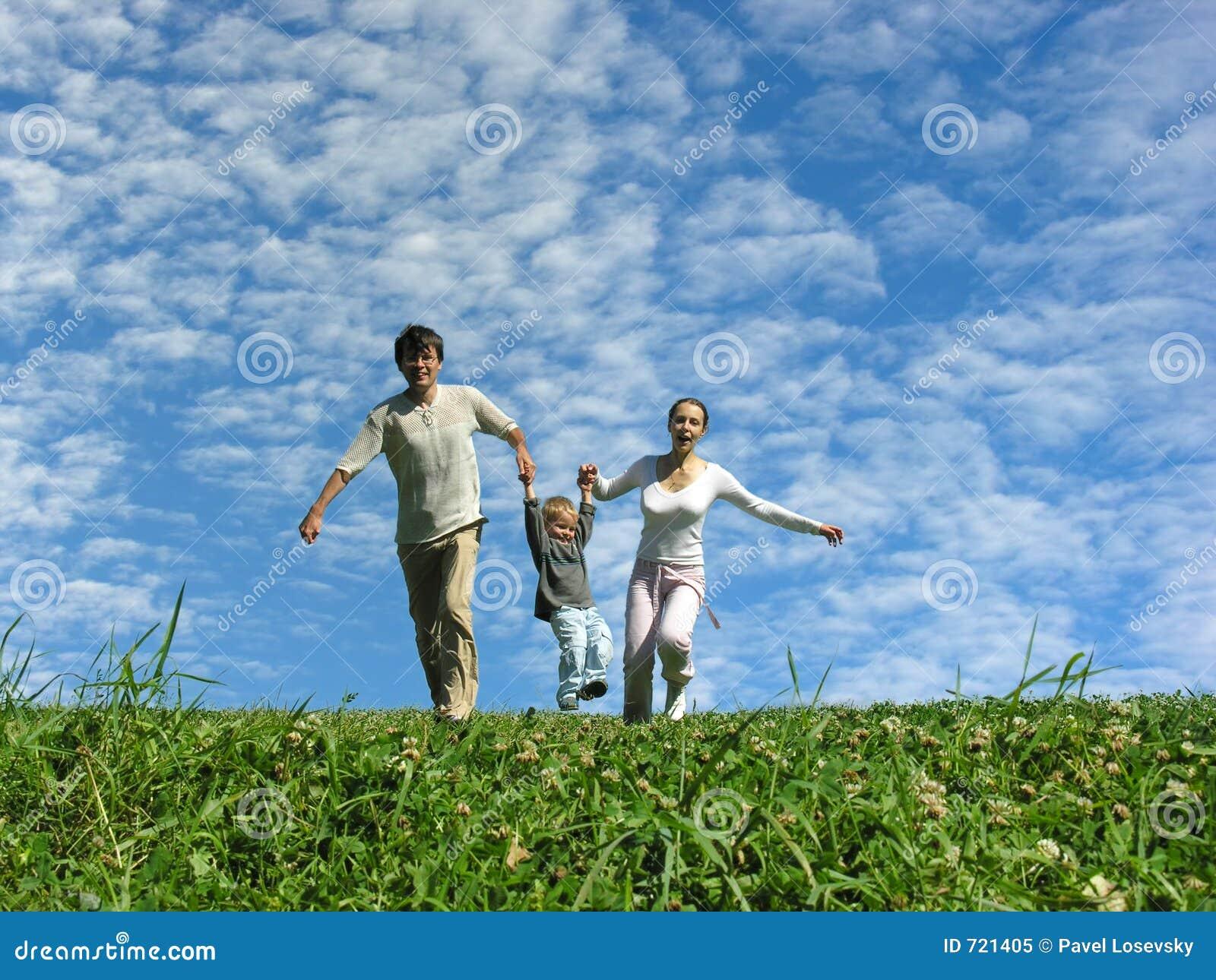 Familie op kruid onder blauwe hemel