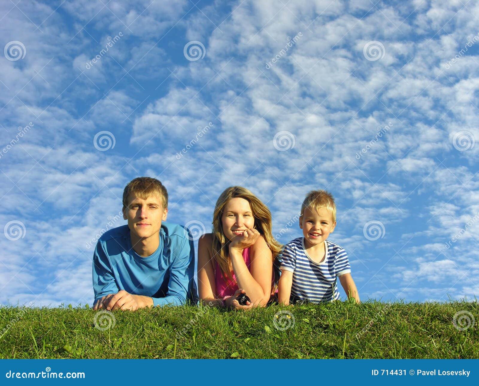 Familie op kruid onder blauwe wolkenhemel