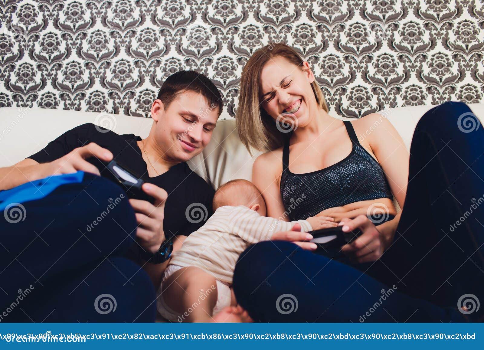 Familie sitzt auf der Couch, ein Mann spielt in der Konsole