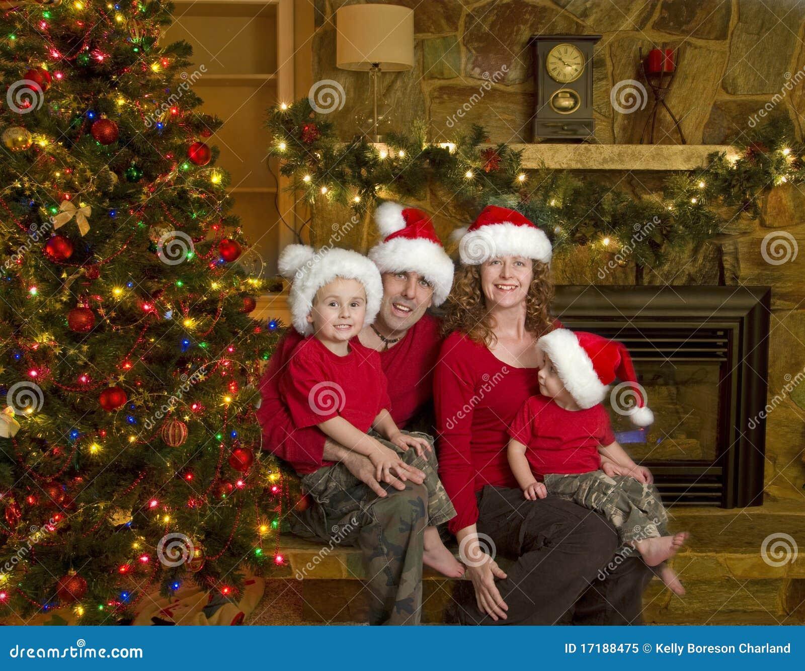 Familie sitzt neben Weihnachtsbaum