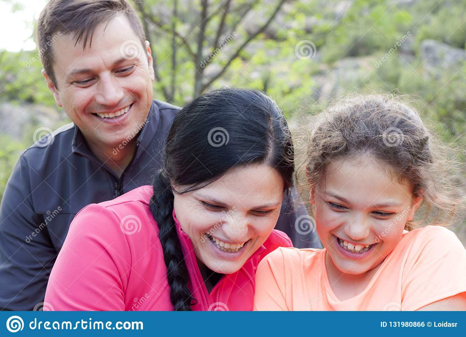 Familie van drie die in de berg lachen