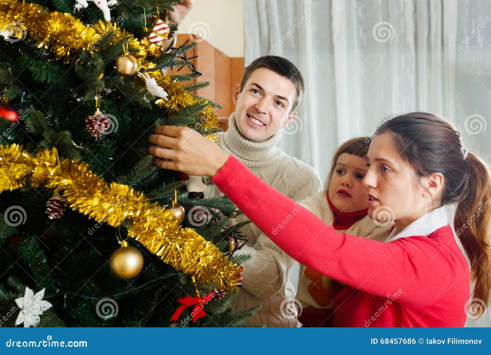 Familie van drie die voor Kerstmis voorbereidingen treffen