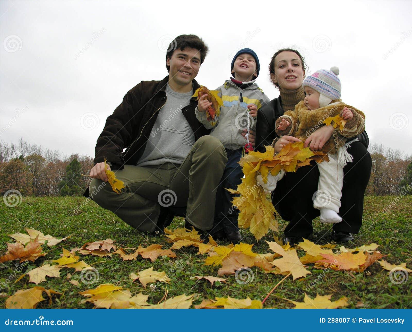 Familie van vier met de herfstbladeren