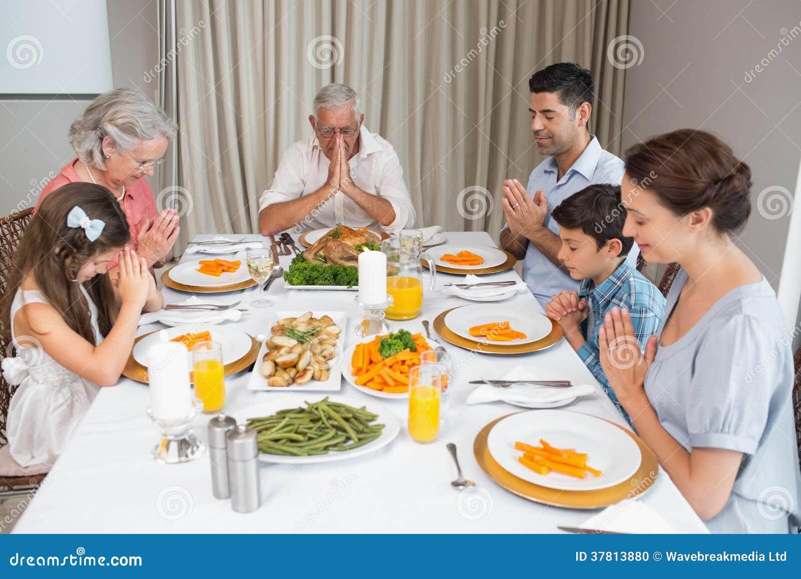 Familie van zes die gunst zeggen vóór maaltijd bij eettafel