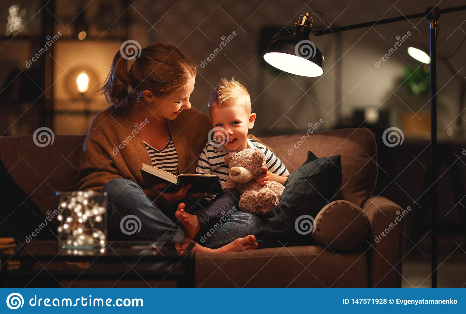 Familie vor schlafen gehender Mutter liest zu ihrem Kindersohnbuch nahe einer Lampe am Abend