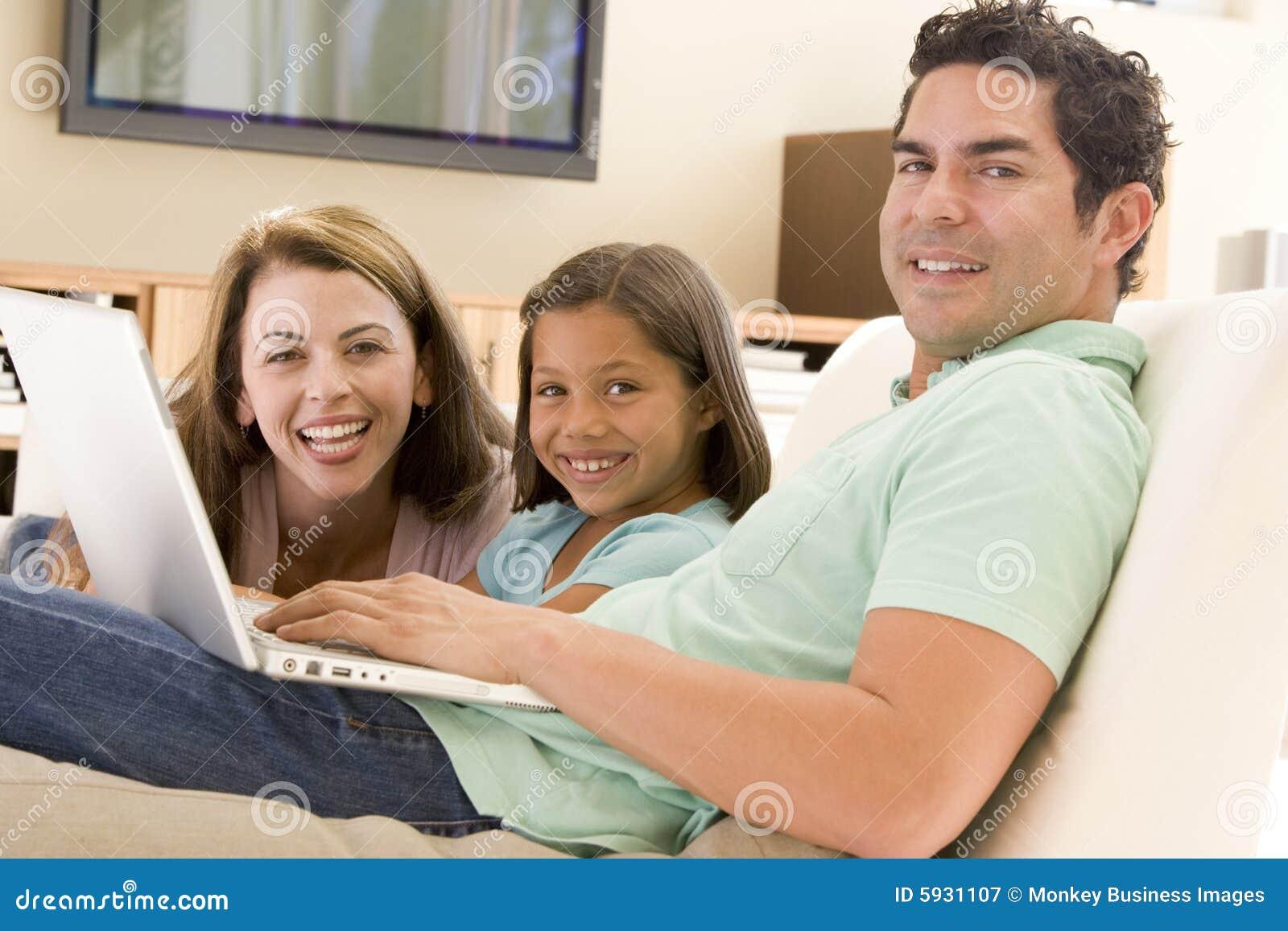 Familie in woonkamer met laptop