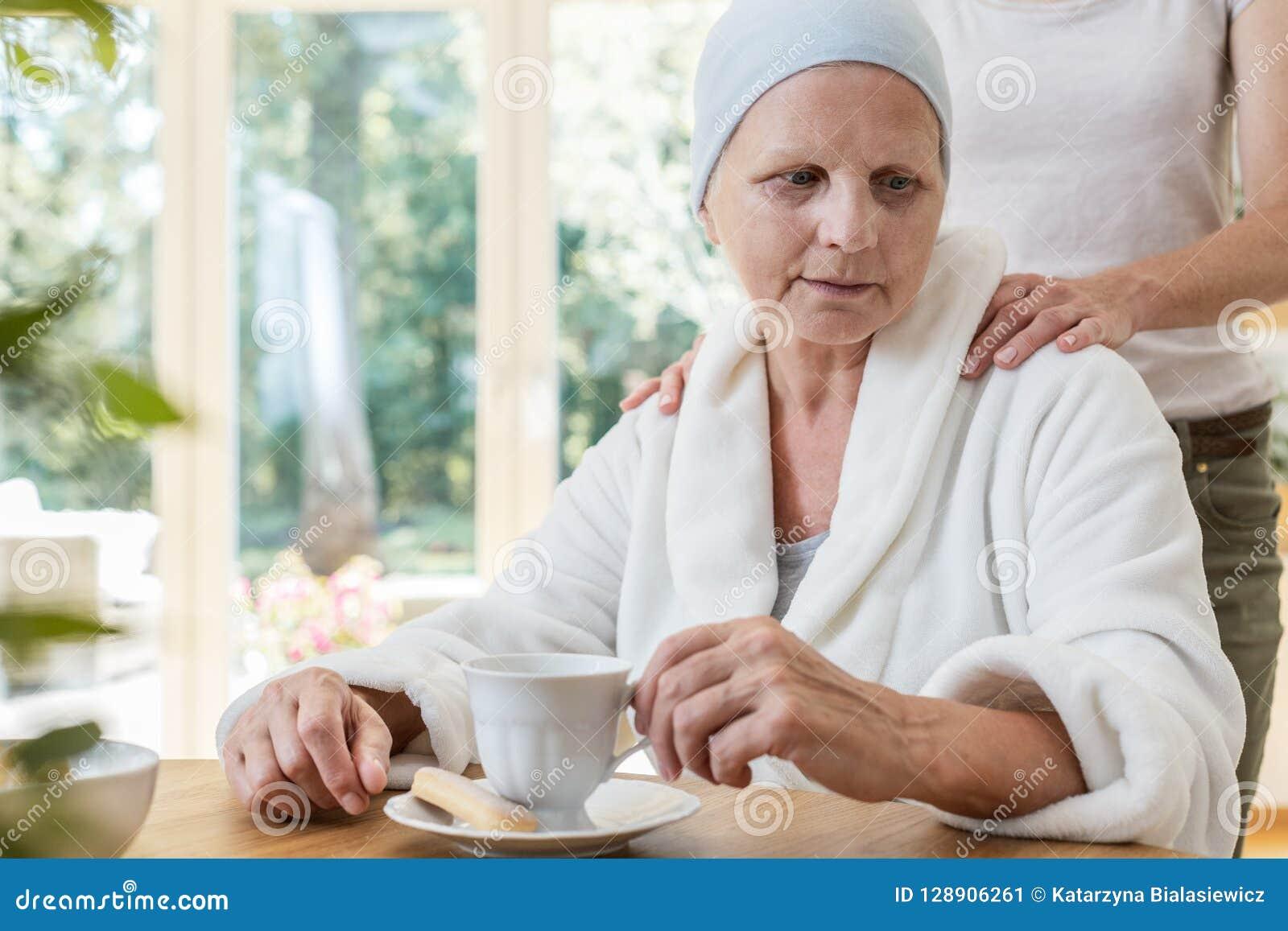 Familielid ondersteunend ziek bejaarde met kanker