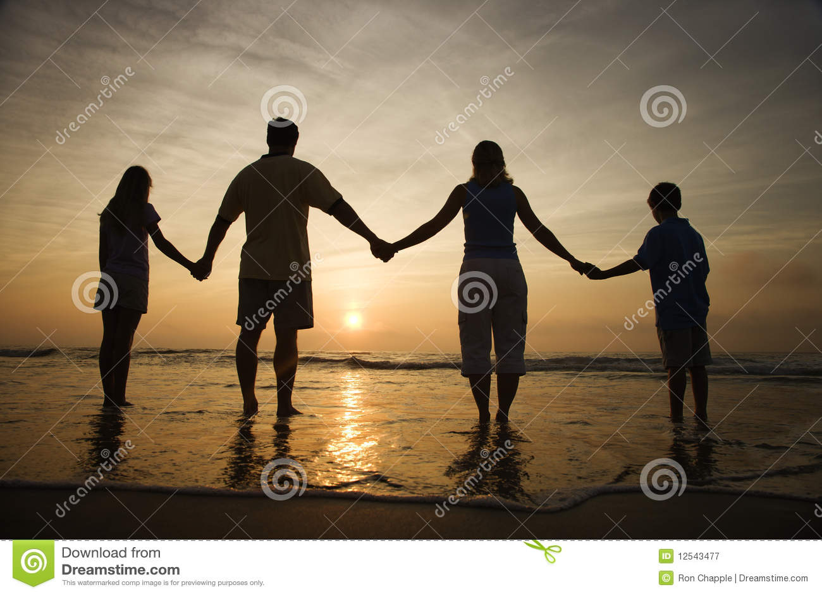 Familien-Holding-Hände auf dem Strand, der den Sonnenuntergang überwacht