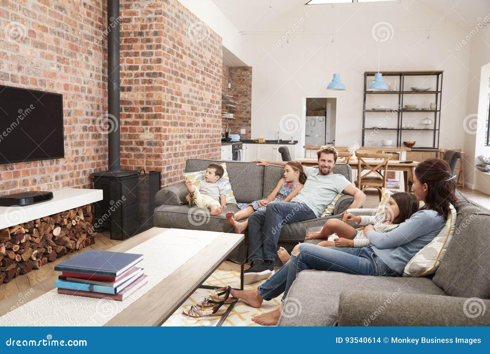 Familien-Sit On Sofa In Open-Plan-Aufenthaltsraum-aufpassendes Fernsehen