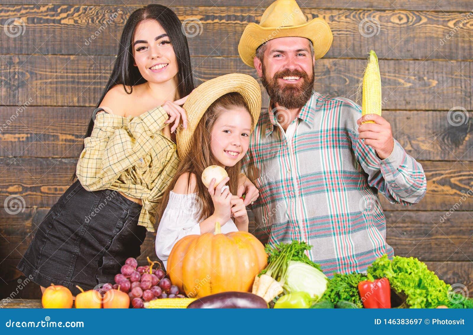 Familienbauernhofkonzept Familienlandwirte mit h?lzernem Hintergrund der Ernte E
