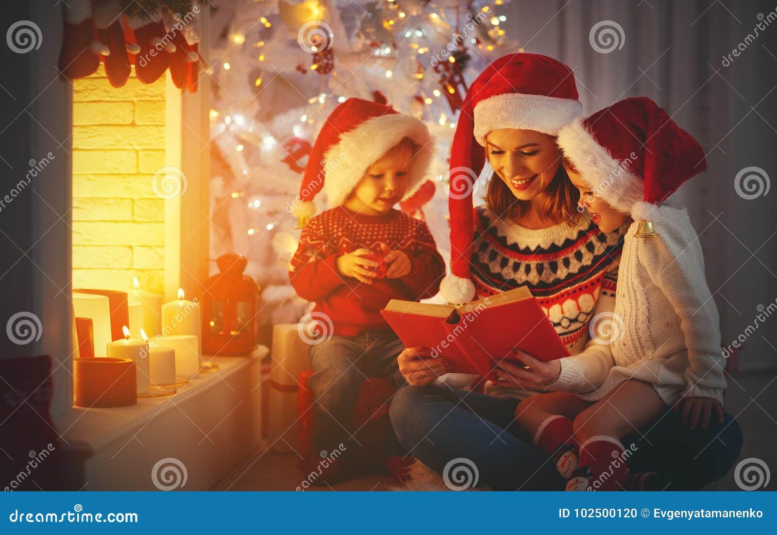 Familienmutter und -kinder lasen ein Buch am Weihnachten nahe firep