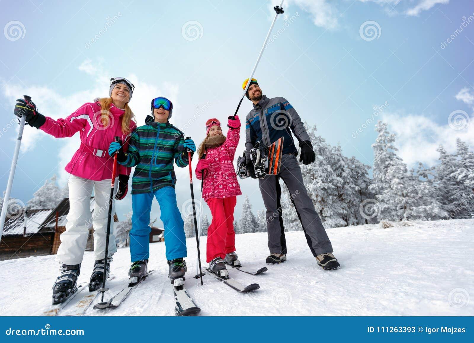 Familiensportskifahren und Snowboardingzeit am sonnigen Tag