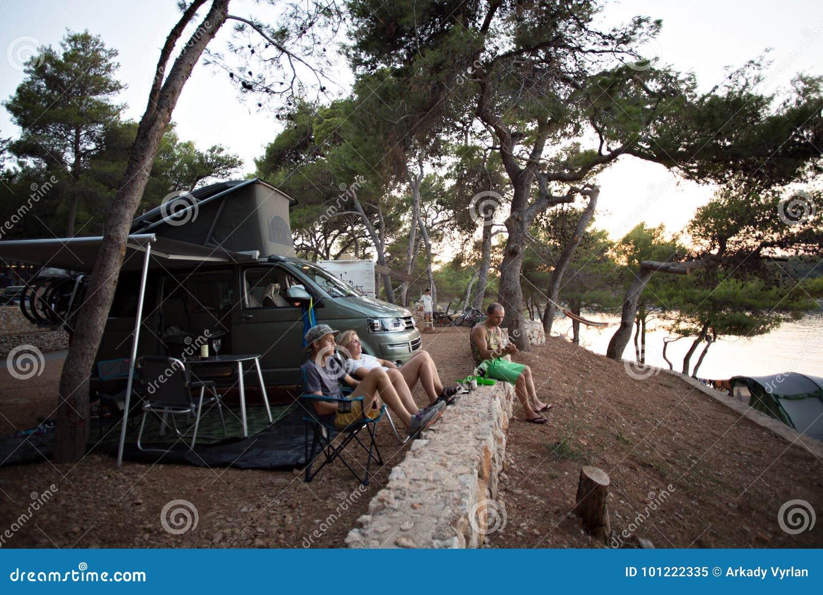 Familierust in bos naast het kamperen bestelwagen