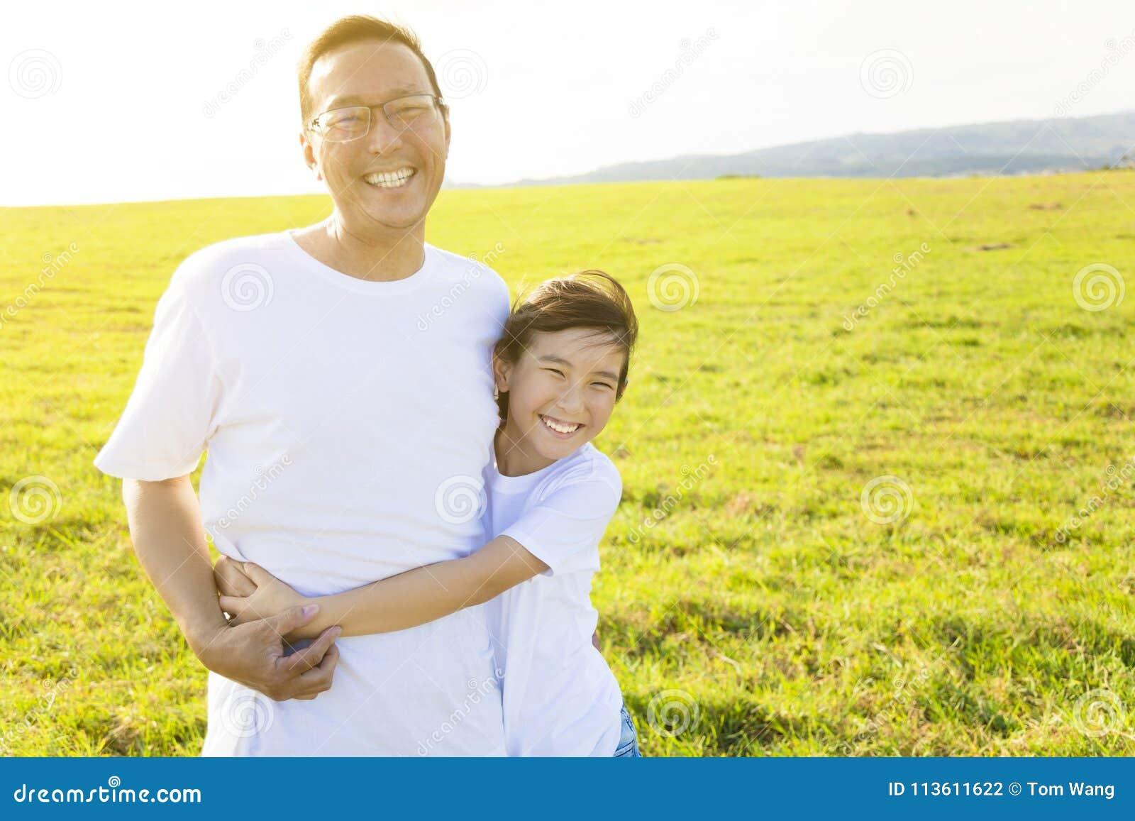 Familievader en kind die op weide koesteren