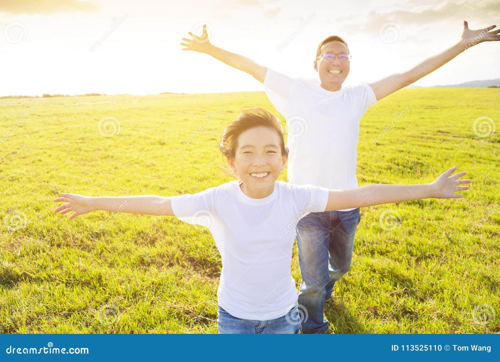 Familievader en kind die op weide lopen