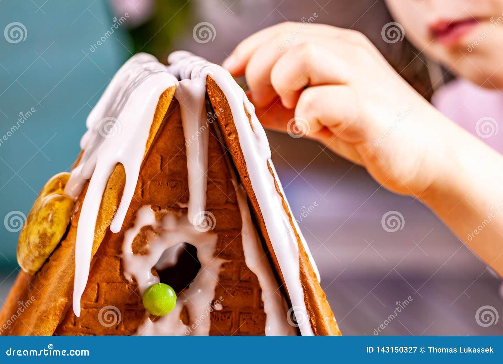 Familiy que construye una casa dulce del pan del jengibre